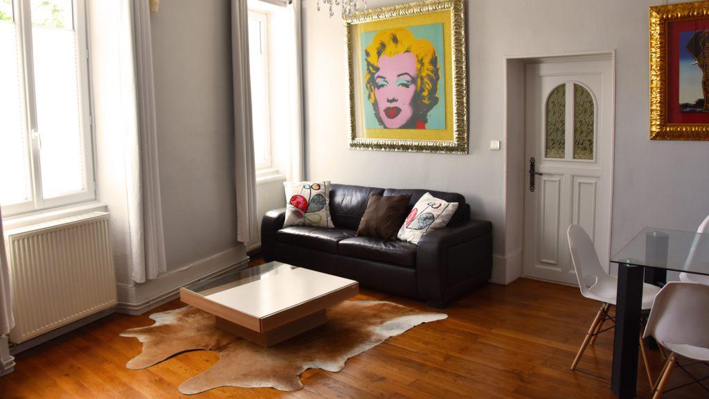 Salon spacieux et accueillant avec un canapé en cuir, table basse et fauteuil attenant
